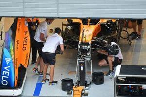 Сотрудники McLaren работают над болидом McLaren MCL35 в боксах
