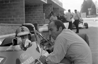 Frank Williams habla con Piers Courage, De Tomaso 308 Ford en el pit lane