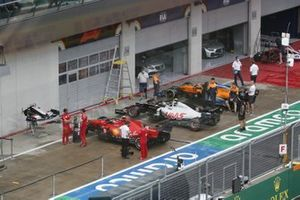 The cars of Charles Leclerc, Ferrari SF1000, Kevin Magnussen, Haas VF-20, and Carlos Sainz Jr., McLaren MCL35