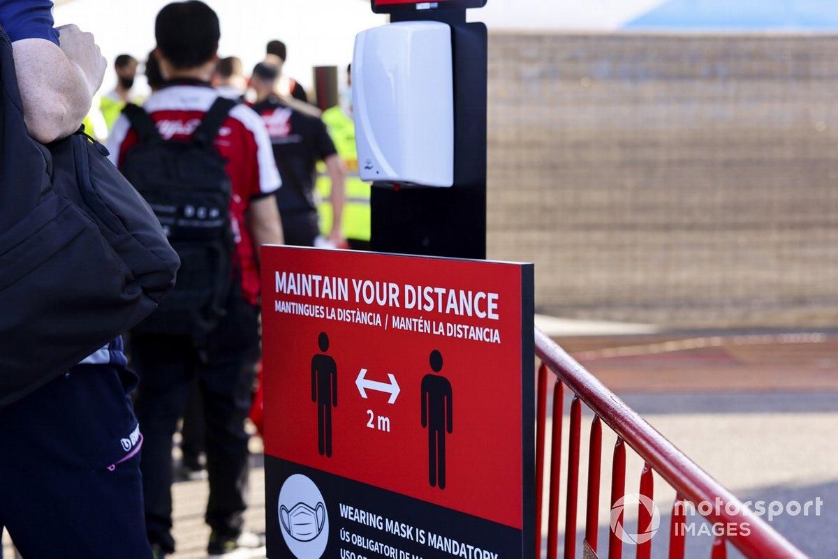 Una señal que recuerda la necesidad de mantener la sana distancia en el paddock
