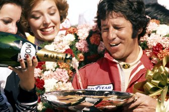 Race winner Mario Andretti, Lotus celebrates on the podium by having his trophy filled with champagne