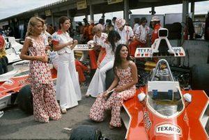 Chicas Marlboro y mecánicos McLaren con McLaren M23 Fords en los fosos
