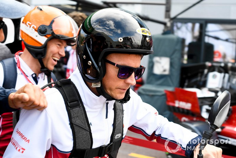 Kimi Raikkonen, Alfa Romeo Racing and Mark Arnell, Personal Trainer ride a moped