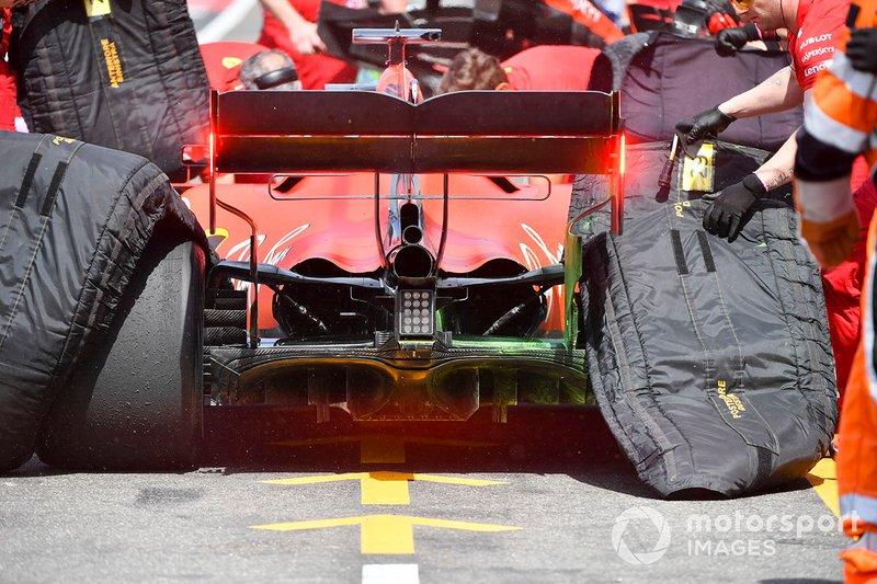 Los mecánicos retiran los calentadores de neumáticos del coche de Sebastian Vettel, Ferrari SF90, en el pit lane.