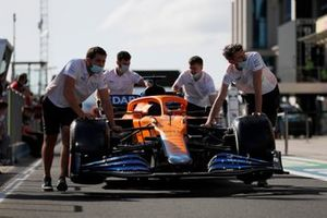 Monteurs duwen de auto van Daniel Ricciardo, McLaren MCL35M, langs de pitlane
