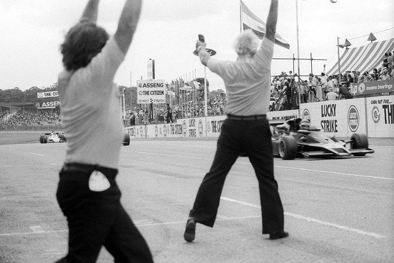 Colin Chapman, propietario del equipo Lotus, celebra mientras Ronnie Peterson, Lotus 78 cruza la línea de meta para ganar el GP