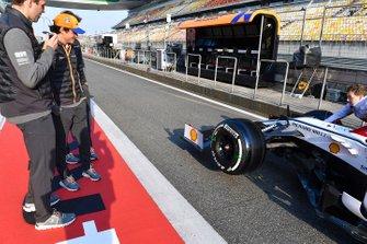 Carlos Sainz Jr., McLaren, observa el Alfa Romeo Racing C38