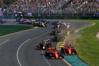 Sebastian Vettel, Ferrari SF90, leads Charles Leclerc, Ferrari SF90, Max Verstappen, Red Bull Racing RB15, Kevin Magnussen, Haas F1 Team VF-19, Romain Grosjean, Haas F1 Team VF-19, Nico Hulkenberg, Renault F1 Team R.S. 19, and the remainder of the field through the first corner