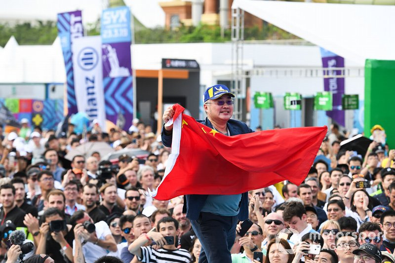 A DS TECHEETAH representative on the podium with a flag of the People's Republic of China