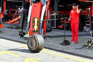 Ferrari Mechanic with a Pirelli tyre in the pit box
