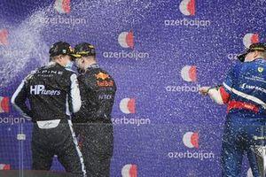 Oscar Piastri, Prema Racing, 2nd position, Juri Vips, Hitech Grand Prix, 1st position, and Robert Shwartzman, Prema Racing, 3rd position, spray champagne on the podium
