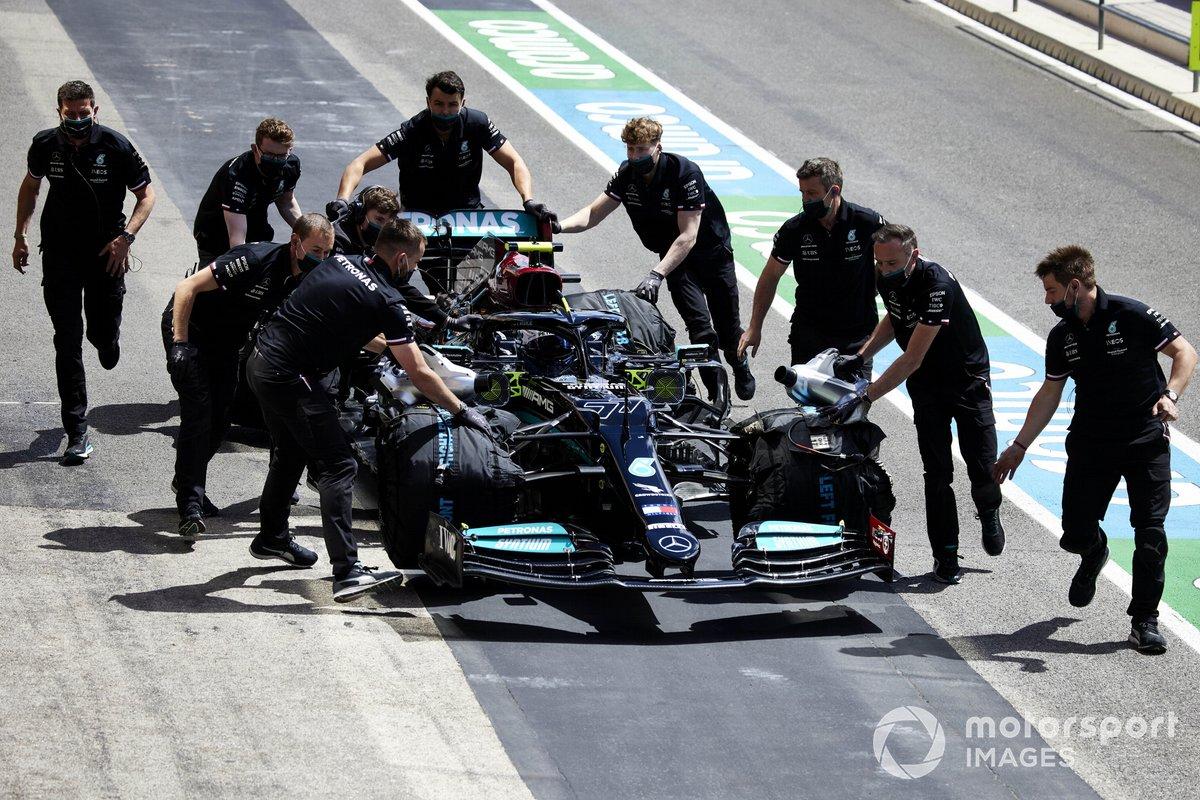Mechanics move the car of Valtteri Bottas, Mercedes W12