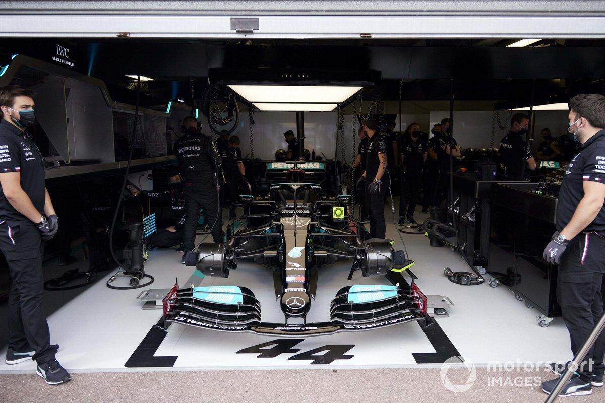 Mecánicos con el coche de Lewis Hamilton, Mercedes W12, en el garaje