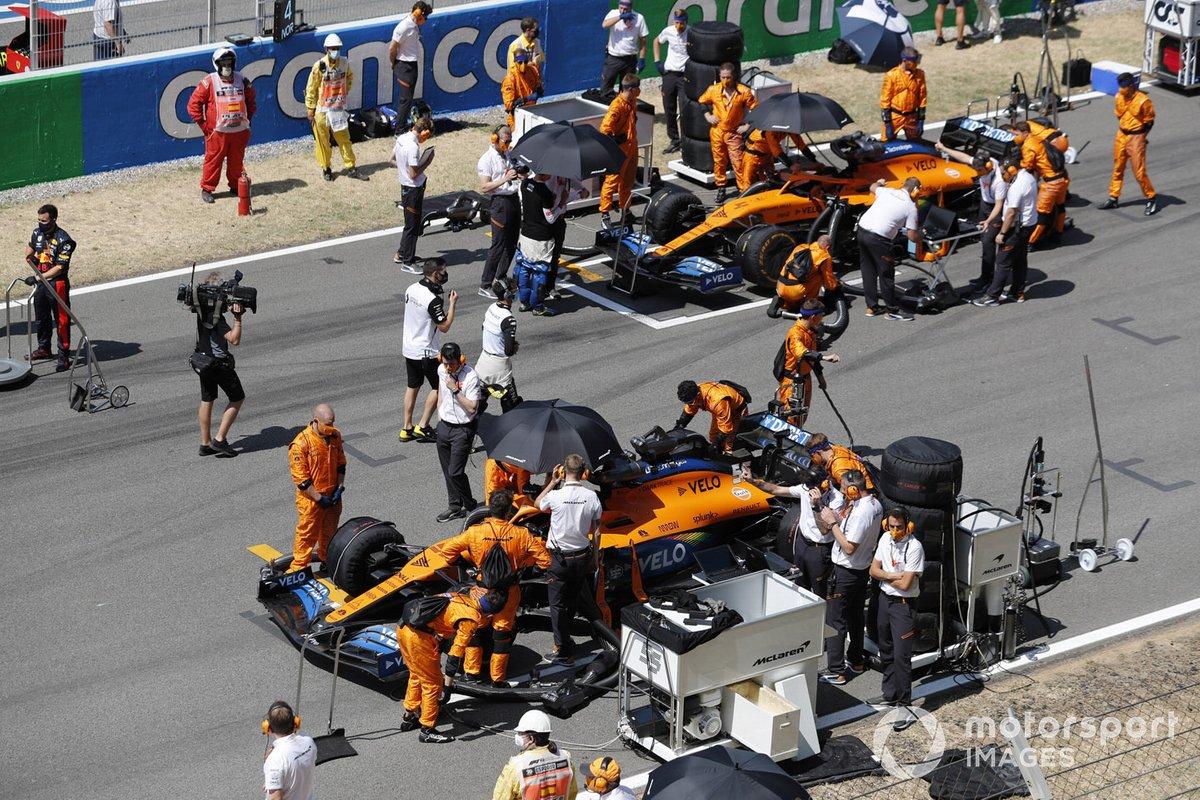 Los mecánicos preparan los coches de Carlos Sainz Jr., McLaren MCL35, Lando Norris, McLaren MCL35, en la parrilla