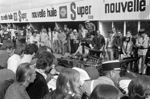 A mechanic pushes Emerson Fittipaldi's Lotus 72D Ford through the pit lane