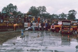 Marshals and fire crews attend to the crashed cars of Wilson Fittipaldi, Fittipaldi FD01 Ford, and James Hunt, Hesketh Ford 308