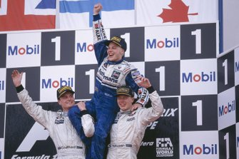 Jacques Villeneuve, Williams, celebrates becoming World Champion with McLaren Mercedes drivers David Coulthard and Mika Hakkinen