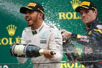 Lewis Hamilton, Mercedes AMG, sprays champagne with Max Verstappen, Red Bull, on the podium