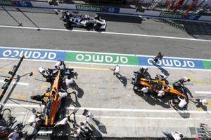 Carlos Sainz Jr., McLaren MCL35, and Lando Norris, McLaren MCL35, are returned to the garage as Daniil Kvyat, AlphaTauri AT01, passes