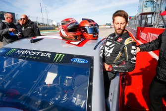 Romain Grosjean, Haas F1, gets into the car of NASCAR Cup driver Tony Stewart
