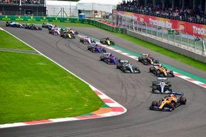 Carlos Sainz Jr., McLaren MCL34, leads Lewis Hamilton, Mercedes AMG F1 W10, Lando Norris, McLaren MCL34, Valtteri Bottas, Mercedes AMG W10, Max Verstappen, Red Bull Racing RB15, Daniil Kvyat, Toro Rosso STR14, and the remainder of the field on the opening lap