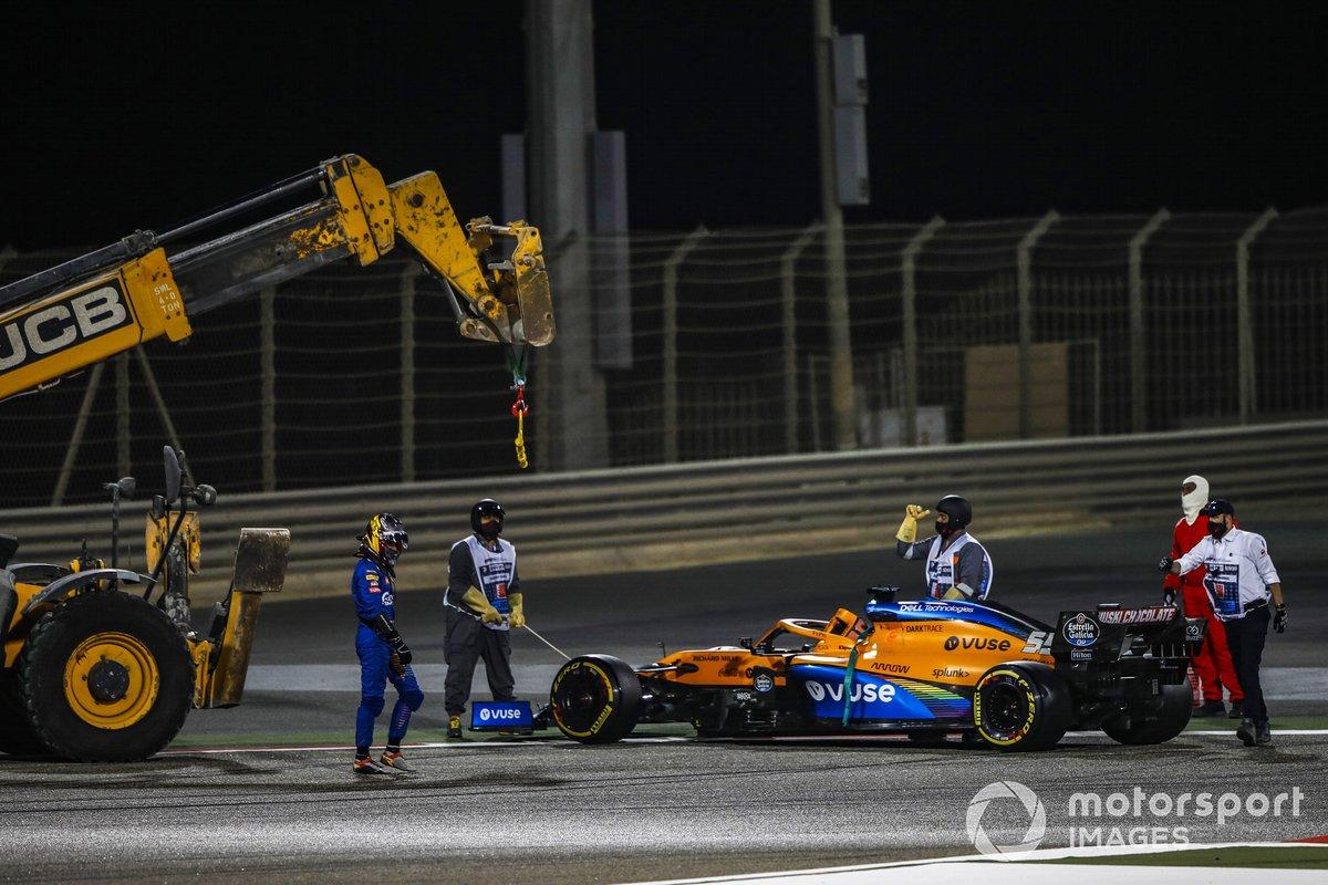 Los oficiales de pista retiran el coche de Carlos Sainz Jr., McLaren MCL35, después de que se detuviera por problemas mecánicos