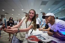 Lewis Hamilton, Mercedes AMG F1, poses for a selfie, a fan