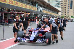 Mecánicos de la Scuderia Toro Rosso empujan el coche de la Scuderia Toro Rosso STR12