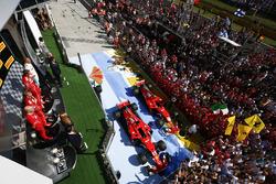 Huge crowds of team personnel gather beneath the podium to cheer for Race winner Sebastian Vettel, Ferrari, Second place Kimi Raikkonen, Ferrari, Third place Valtteri Bottas, Mercedes AMG F1