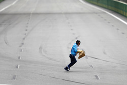 A marshal collects debris from the track