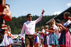 Daniel Ricciardo, Red Bull Racing, gives a thumbs up as he walks down a corridor of dirndl wearing grid girls