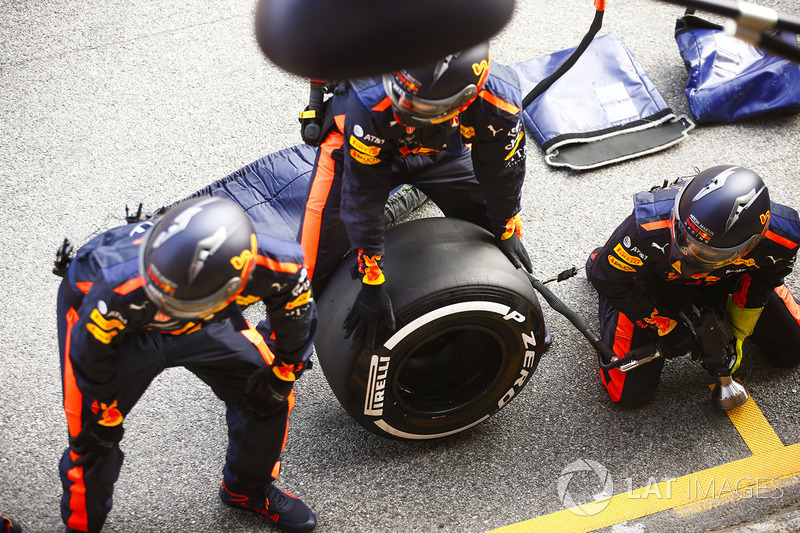 Red Bull mechanics wait outside of their garage with a Pirelli tyre