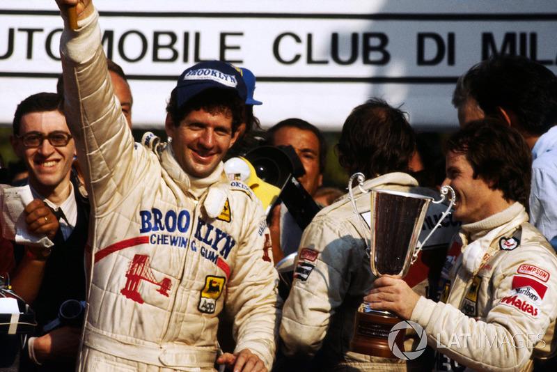 El campeón del mundo Jody Scheckter celebra su título en el podio con Gilles Villeneuve, Ferrari