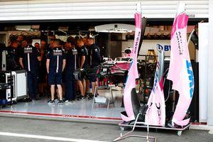 Des mécaniciens rassemblés dans le garage de Force India près de la monoplace de Sergio Perez Force India VJM11