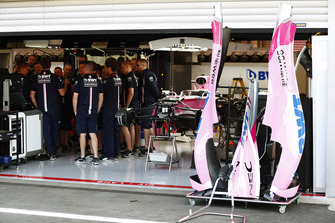 Mechanics gather in the Force India garage, next to the Sergio Perez Force India VJM11