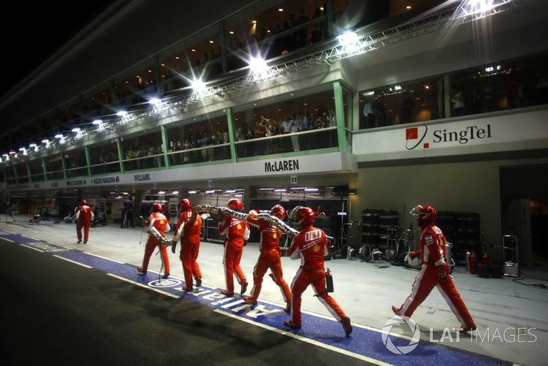 Les mécaniciens Ferrari ramènent le tuyau de ravitaillement en essence au garage