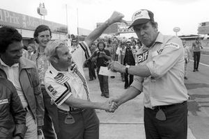 Teddy Mayer, McLaren Team Owner hands over a cheque to Ken Tyrrell, Tyrrell Team Owner after losing a pit stop tyre change competition