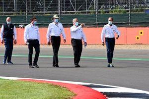 FIA personnel walk the track