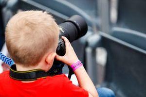Un tifoso scatta delle foto all'azione in pista, dalla tribuna