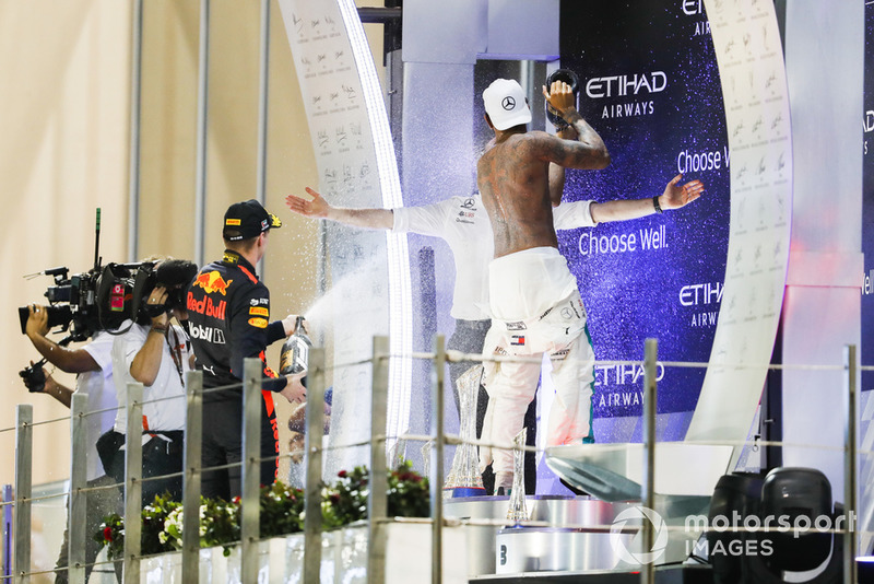 Lewis Hamilton, Mercedes AMG F1, 1st position, takes his overalls down to the waist as Max Verstappen, Red Bull Racing, 3rd position, sprays Rose Water