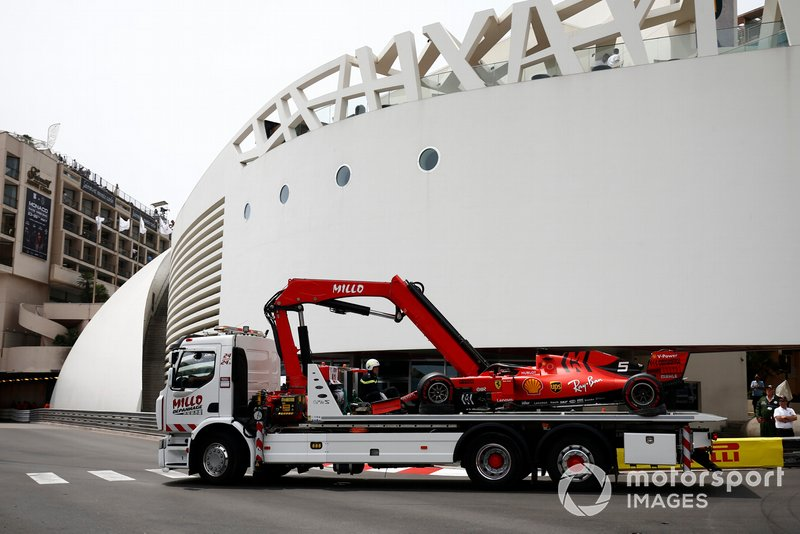 A truck returns the crashed Sebastian Vettel Ferrari SF90 back to the pit lane after FP3