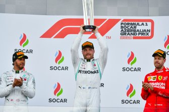 Valtteri Bottas, Mercedes AMG F1, 1st position, lifts his trophy to applause from Lewis Hamilton, Mercedes AMG F1, 2nd position, and Sebastian Vettel, Ferrari, 3rd position