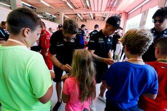 Romain Grosjean, Haas F1, y Kevin Magnussen, Haas F1, firman autógrafos