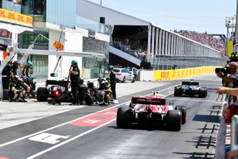 Lewis Hamilton, Mercedes AMG F1 W10, precede Antonio Giovinazzi, Alfa Romeo Racing C38, fuori dai box, mentre Valtteri Bottas, Mercedes AMG W10, effettua un pit stop durante le Qualifiche
