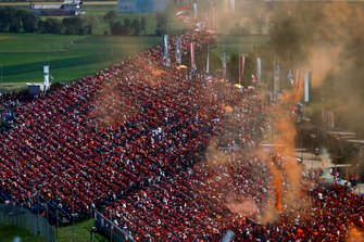 A sea of orange and orange smoke flares in a grandstand in support of Dutchman Max Verstappen, Red Bull Racing