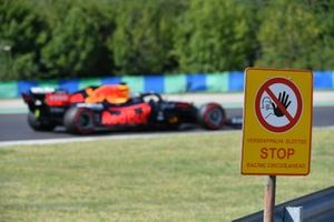 Max Verstappen, Red Bull Racing RB16B, passes a track side sign
