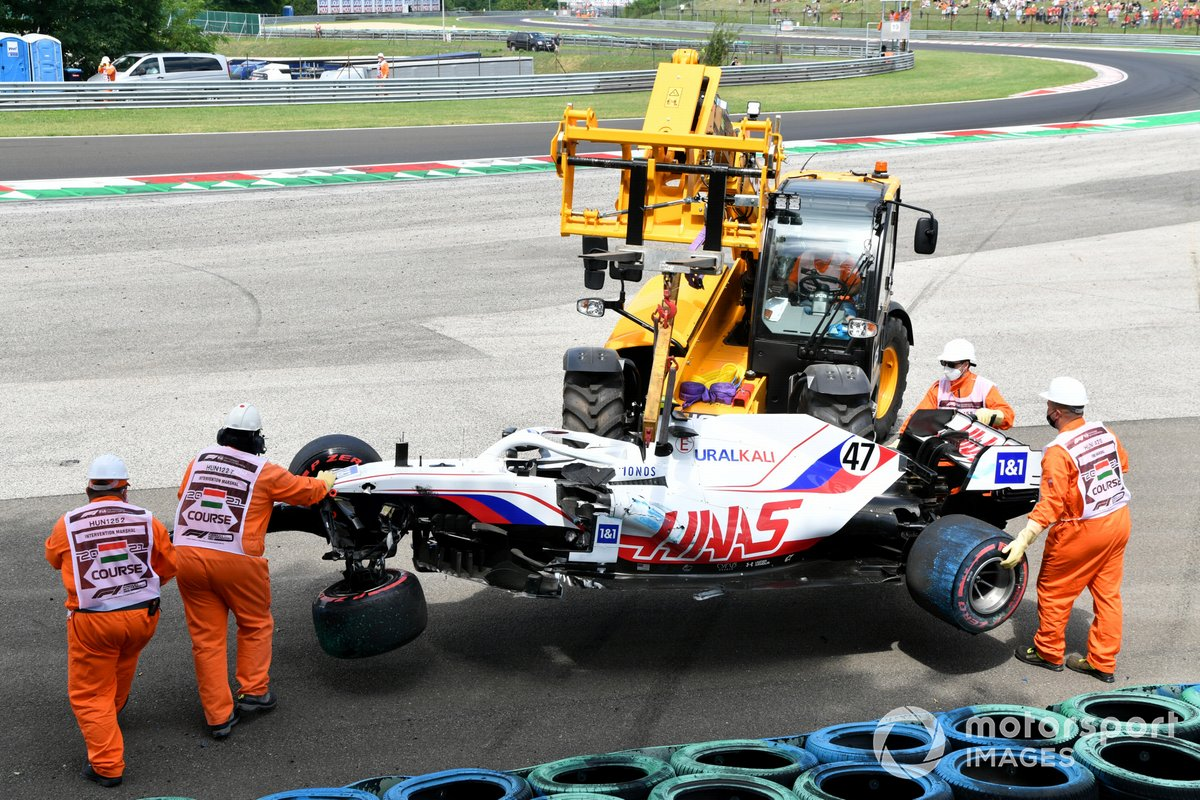 Судьи убирают разбитую машину Мика Шумахера, Haas VF-21, после аварии в тренировке