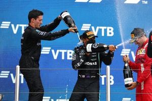 Lewis Hamilton, Mercedes, 1st position, the Mercedes trophy delegate, Carlos Sainz Jr., Ferrari, 3rd position, and Max Verstappen, Red Bull Racing, 2nd position, celebrate with Champagne on the podium