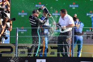 Daniel Ricciardo, McLaren, 1st position, and Valtteri Bottas, Mercedes, 3rd position, spray Champagne over Zak Brown, CEO, McLaren Racing, on the podium