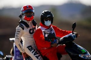 Pierre Gasly, AlphaTauri on a scooter with a marshal after retiring